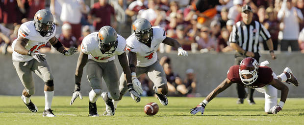 Texas A&M's Kenric McNeal watches as Oklahoma State's Justin Gilbert (4) recovers McNeal's fumble next to Markelle Martin (10) and Brodrick Brown (19) in the third quarter of their game Saturday in College Station, Texas. The fumble and recovery turned the tide of the game, leading OSU to a 30-29 win in College Station, Texas. Photo by Nate Billings, The Oklahoman