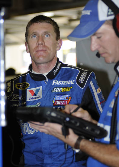 Carl Edwards looks at lap times in the garage after practice for the NASCAR Sprint Cup Series auto race at Texas Motor Speedway, Friday, April 13, 2012, in Fort Worth, Texas. (AP Photo/Larry Papke)