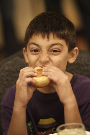 Kian Azarsepandan eats bites into a roll at the Edmond Community Thanksgiving event at The University of Central Oklahoma in  Edmond, Thursday  November 22, 2012. Photo By Steve Gooch, The Oklahoman