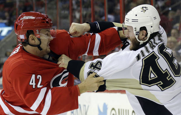 Carolina Hurricanes' Brett Sutter, left, and Pittsburgh Penguins' Joe Vitale, right, fight during the first period of an NHL hockey game in Raleigh, N.C., Monday, Oct. 28, 2013. (AP Photo/Gerry Broome)