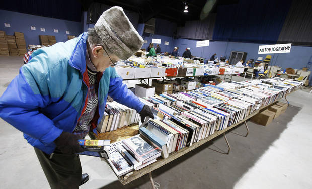 Larry Eberhardt sorts books on the autobiography table for the annual Friends of the Library Book Sale.  PHOTOS BY PAUL B. SOUTHERLAND, THE OKLAHOMAN