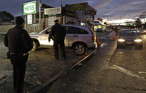 Police officers help keep order at a Hess gas station in the Brooklyn borough of New York where gas is still scarce, Thursday, Nov. 8, 2012. Fuel shortages and distribution delays that led to gas hoarding have prompted New York City and Long Island to initiate an even-odd gas rationing plan which begins Friday at 6 a.m. in New York and 5 a.m. in Long Island. The line at this station was about an hour and 40 minutes, according to drivers waiting for gas. (AP Photo/Kathy Willens)
