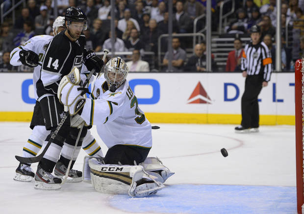 Dallas Stars goalie Kari Lehtonen, right, of Finland, and Los Angeles Kings right wing Justin Williams watch the puck as it barely misses the goal during the second period of their NHL hockey game, Thursday, March 21, 2013, in Los Angeles. (AP Photo/Mark J. Terrill)