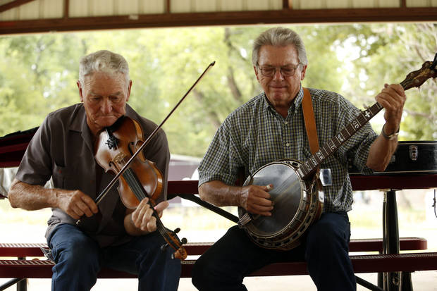 Verlon Stidham, playing fiddle, and Hiram McMasters, both with the band Cast Iron, join a jam session at the Bluegrass Festival on Saturday in Blanchard.     Photos by Steve Sisney, The Oklahoman