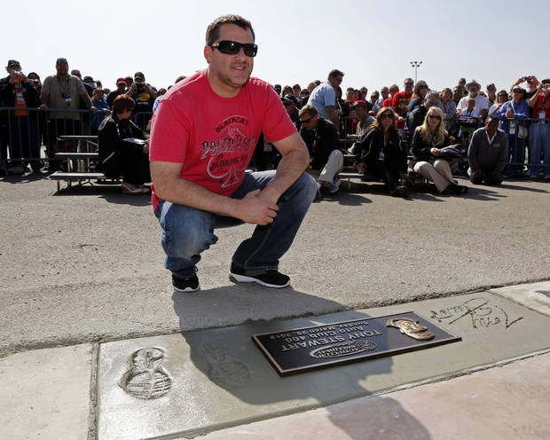 Two-time winner Tony Stewart poses with his footprints and signature with a plaque in concrete in the Auto Club Speedway walk of fame before practice and qualifying for the NASCAR Sprint Cup series Auto Club 400 race, in Fontana, Calif., Friday, March 22, 2013. (AP Photo/Reed Saxon)