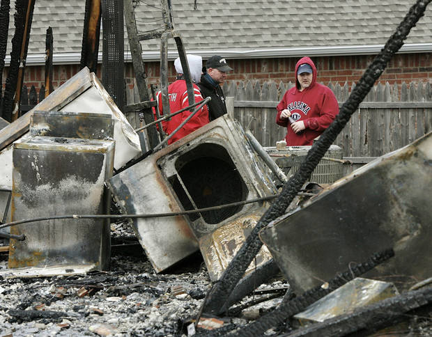 David Dolney, far right, and relatives look at damage to the home where he and his wife, Niki, lived in Oakwood East Royale neighborhood, 11365 Queensland Ct.  The house was one of numerous structures destroyed in Thursday's wildfires. Photo by Jim Beckel, The Oklahoman