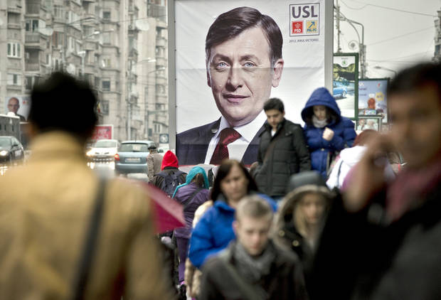 People walk by a large electoral poster of the ruling Social Liberal Union in Bucharest, Romania, Wednesday, Dec. 5, 2012. Romania will hold parliamentary elections on Dec. 9, 2012. (AP Photo/Vadim Ghirda)