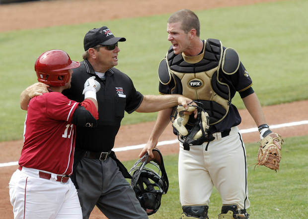 Oklahoma's Cody Reine and Missouri's Ben Turner are separated by the home plate umpire during the Big 12 baseball championship game between the University of Oklahoma and Missouri at the Chickasaw Bricktown Ballpark in Oklahoma City,  Sunday, May 27, 2012. Photo by Sarah Phipps, The Oklahoman.