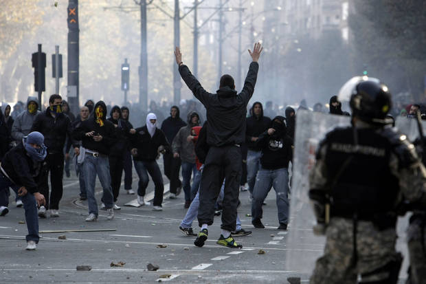 FILE - In this Sunday, Oct. 10, 2010 file photo, protesters throw stones at riot police protecting a gay pride march in Belgrade, Serbia. Serbia's police on Wednesday, Oct. 3, 2012, banned a gay pride march in Belgrade planned for the weekend, citing security concerns but also complying with a request from Serbia's Christian Orthodox church. (AP Photo/Marko Drobnjakovic, File)