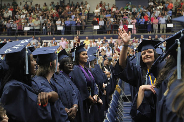 Kristin Walker, an education major, waves to her family during a University of Central Oklahoma graduation ceremony in Edmond, Friday, May 4.  Photo by Garett Fisbeck, For The Oklahoman
