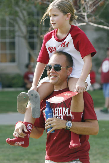 Max Ross gives Ellzabeth Ross, 7, a ride to the stadium before the college football game between the University of Oklahoma Sooners (OU) and the Tulsa University Hurricanes (TU) at the Gaylord Family-Memorial Stadium on Saturday, Sept. 3, 2011, in Norman, Okla. 