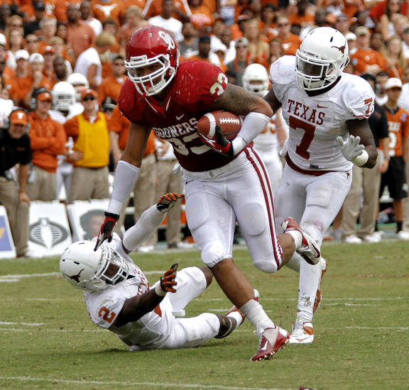 OU's Trey Millard (33) runs past UT's Mykkele Thompson (2) and Demarco Cobbs (7) during the Red River Rivalry college football game between the University of Oklahoma (OU) and the University of Texas (UT) at the Cotton Bowl in Dallas, Saturday, Oct. 13, 2012. Photo by Chris Landsberger, The Oklahoman