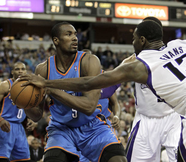 Sacramento Kings guard Tyreke Evans, right, hits the ball away from Oklahoma City Thunder center Serge Ibaka, of the Republic of Congo, during the first quarter of  an NBA basketball game in Sacramento, Calif., Friday, Jan. 25, 2013. (AP Photo/Rich Pedroncelli) ORG XMIT: SCA107