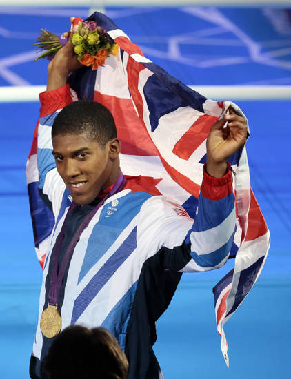 Gold medalist Anthony Joshua of Great Britain poses with his medal after the victory ceremony for the men's super heavyweight over 91-kg boxing medals at the 2012 Summer Olympics, Sunday, Aug. 12, 2012, in London. (AP Photo/Ivan Sekretarev)