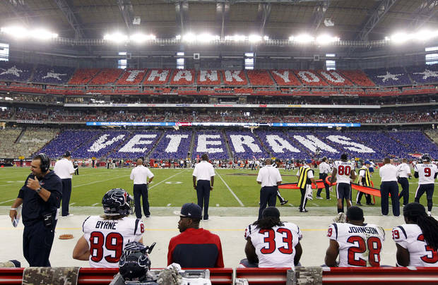 "Fans hold flip cards from their seats thanking veterans during the first half of an NFL football game between the Houston Texans and the Arizona Cardinals, Sunday, Nov. 10, 2013, in Glendale, Ariz. The NFL is celebrating Veterans Day with a league wide ""Salute to Service"" campaign. (AP Photo/Ross D. Franklin)"