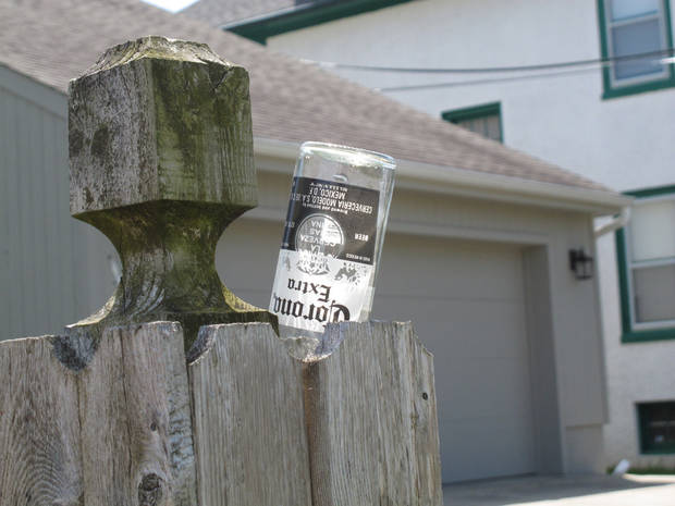 FILE - In this On May 6, 2012 file photo, a beer bottle sits wedged into the fence of a homeowner near the Point Pleasant Beach, N.J. boardwalk.  The town and its largest boardwalk bar operator have reached a deal to drop an earlier bar closing law in return for the company dropping lawsuits against the town, and contributing up to $1 million toward the cost of fixing the storm-damaged boardwalk. The town last year  took a number of steps to combat rowdy behavior by tourists drawn to boardwalk bars. (AP Photo/Wayne Parry)