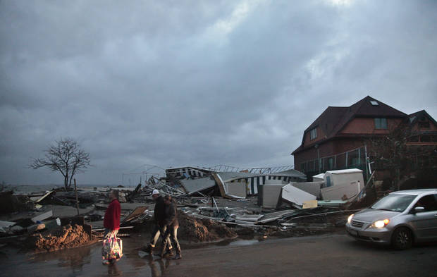 People walk through the houses destroyed in the aftermath of yesterday's storm surge from superstorm Sandy, Tuesday, Oct. 30, 2012, in Coney Island's Sea Gate community in New York. (AP Photo/Bebeto Matthews) ORG XMIT: NYBM118