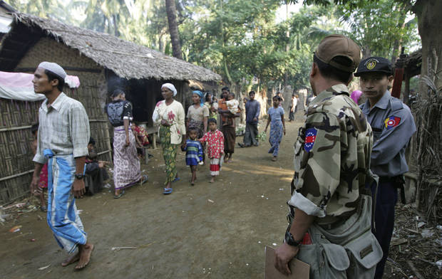 In this photo taken on Nov. 10, 2012, Muslim refugees walk as Myanmar police officers stand guard at Sin Thet Maw relief camp in Pauktaw township, Rakhine state, western Myanmar.  Myanmar�s government has launched a major operation aimed at verifying the citizenship of Muslims in western Rakhine state, the coastal territory that has been torn apart by Buddhist-Muslim violence since June.  Questions over whether the region's Muslim Rohingya population qualify for citizenship are at the heart of a crisis that has killed nearly 200 people and displaced 110,000 more.    (AP Photo/Khin Maung Win)
