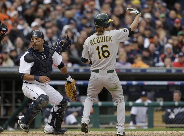 Oakland Athletics' Josh Reddick (16) signals for teammate Yoenis Cespedes to run from third as Detroit Tigers catcher Gerald Laird chases a wild pitch during the eighth inning of Game 2 of the American League division baseball series, Sunday, Oct. 7, 2012, in Detroit. (AP Photo/Paul Sancya)
