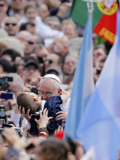 Pope Francis hugs a child after celebrating his first Easter Mass in St. Peter's Square at the Vatican, Sunday, March 31, 2013.  Pope Francis made an Easter Sunday peace plea, saying conflicts have lasted too long in Syria, and between Israelis and Palestinians. (AP Photo/Andrew Medichini)