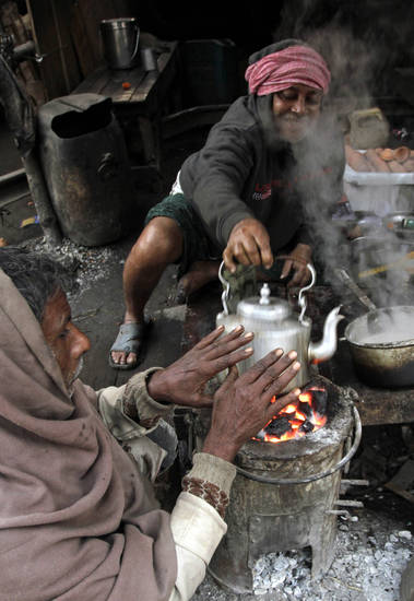 An Indian man warms his hands over a stove at a roadside tea stall on a cold winter morning in Kolkata, India, Friday, Jan. 11, 2013. More than 100 people have died of exposure as several parts of India deal with historically cold temperatures. (AP Photo/Bikas Das)