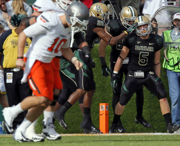The Baylor Bears celebrate an interception returned for a touchdown by Eddie Lackey (5) as OSU quarterback Clint Chelf (10) leaves the field in the first quarter during a college football game between the Oklahoma State University Cowboys (OSU) and the Baylor University Bears at Floyd Casey Stadium in Waco, Texas, Saturday, Dec. 1, 2012. Photo by Nate Billings, The Oklahoman
