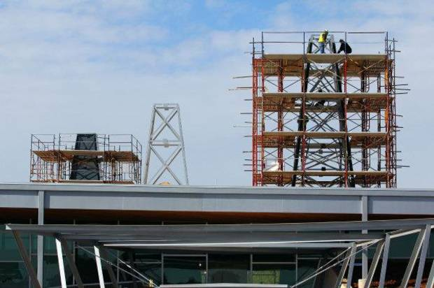 Workers stand on scaffolding to construct a skylight at the top of a faux oil derrick at the newest Metropolitan Library System branch in northwest Oklahoma City. PHOTO BY HUGH SCOTT, FOR THE OKLAHOMAN <strong>HUGH SCOTT</strong>