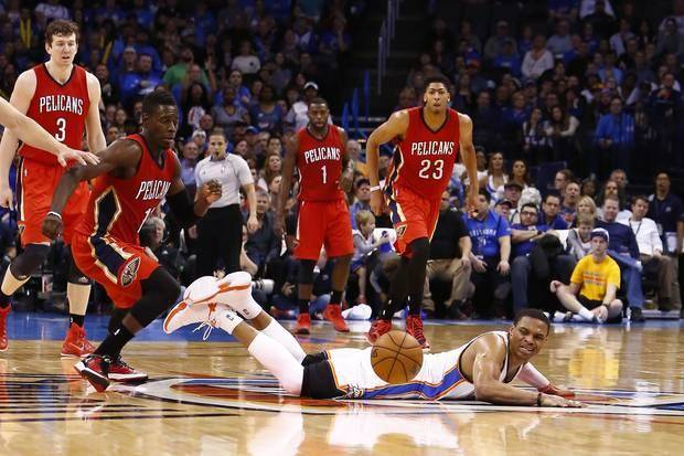 Russell Westbrook watches the ball roll from his grasp as New Orleans' Jrue Holliday bears down for the steal. (Photo by Steve Sisney)