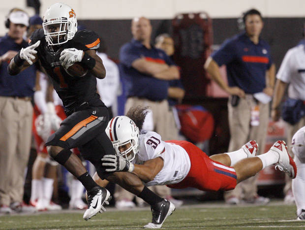 Oklahoma State's Joseph Randle (1) tries to shake Arizona's Sione Tuihalamaka (91) during their game Thursday in Stillwater. PHOTO BY SARAH PHIPPS, The Oklahoman