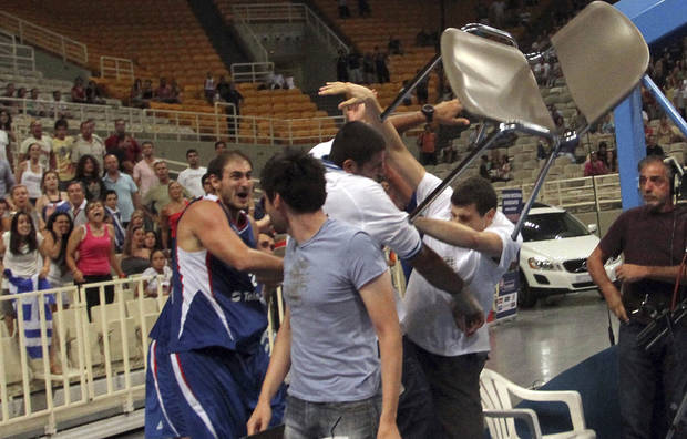 Nenad  Krstic, left, of Serbia throws a chair toward Greece's Yannis Bouroussis, third left, who did not take part in the game, during the Acropolis tournament at the indoor Olympic stadium of Athens, Thursday, Aug. 19, 2010. The friendly basketball tournament finished in a brawl as the last game between Serbia and Greece was abandoned with 2:40 to go when a fight broke out and the benches cleared on Thursday. (AP Photo/Icon, Yiannis Liakos)