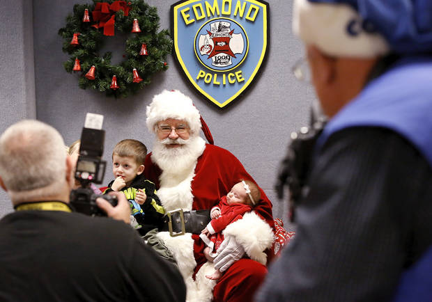 Santa stopped by the Edmond police station Saturday, Dec. 22, 2012, to visit with children, hear their Christmas lists and pose for keepsake photos that were provided for the children by Edmond police department.  Posing for a keepsake photo with Santa is  Jackson Rocamontes, 3,  and his baby sister, Arya, 7 weeks old.  Playing Santa is Boyd Mize, a retired detective with the Edmond police department.  This is the eighth year Mize has donned the Santa suit for the police department's day with Santa.  But Mize said this is the first year he didn't have to wear a fake beard; all the hair on Santa's face is natural this year. Photo by Jim Beckel, The Oklahoman