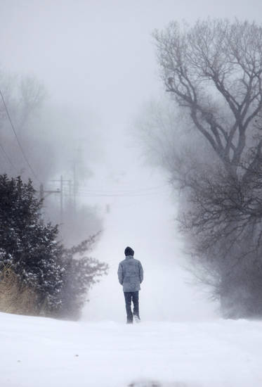 A man walks through deep snow on E. Charter Oak Rd. in Logan County, Oklahoma February  1, 2011. Photo by Steve Gooch, The Oklahoman