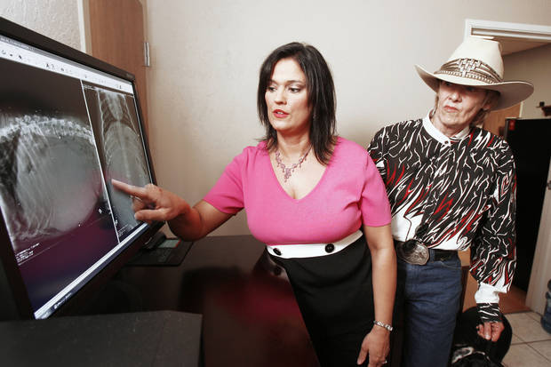 Dr. Donna Woods, who performed surgery to remove a clot the size of a basketball from a hound named Pepper, shows owner Sherri Ellis the X-rays on Tuesday at the Danforth Animal Hospital in Edmond. photo by Paul Hellstern, The Oklahoman