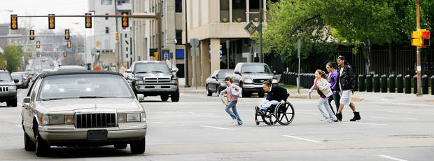 A woman in a wheelchair and children hurry to cross Hudson Avenue between the County Courthouse and City Hall in this 2009 photo. The street has since been narrowed from six to four lanes and converted from one-way to two-way traffic. Photo by Jim Beckel, The Oklahoman Archives
