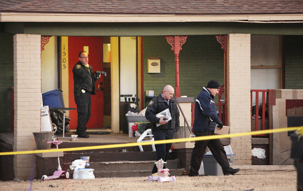 Oklahoma City police officers investigate a shooting scene Friday before sunrise at a home in the 1500 block of NW 39 in Oklahoma City. Photo by Paul B. Southerland, The Oklahoman <strong>PAUL B. SOUTHERLAND - PAUL B. SOUTHERLAND</strong>