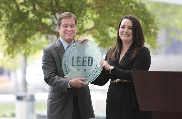 Devon Energy Corp. Executive Chairman Larry Nichols holds a plaque Monday marking Devon Energy Center�s gold certification in Leadership in Energy and Engineering Design. Presenting the plaque is Rhiannon Jacobsen, director of strategic accounts with the U.S. Green Building Council.