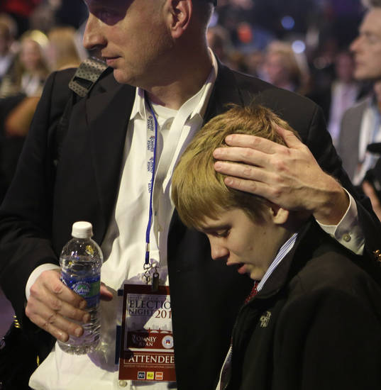 David French, of Columbia, Tenn., consoles his son Austin as they watch vote results displayed on a screen during the election night rally for Republican presidential candidate and former Massachusetts Gov. Mitt Romney, Tuesday, Nov. 6, 2012, in Boston. (AP Photo/David Goldman)