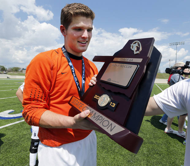 Edmond North goalie David Atkins gets a hand at holding the Class 6A boys state soccer championship trophy following the game between Edmond North and Norman North on Saturday, May 11, 2013 in Noble, Okla.  Photo by Steve Sisney, The Oklahoman