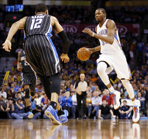 Oklahoma City's Kevin Durant (35) dribbles near Orlando's Tobias Harris (12) during an NBA basketball game between the Oklahoma City Thunder and the Orlando Magic at Chesapeake Energy Arena in Oklahoma City, Friday, March 15, 2013. Photo by Nate Billings, The Oklahoman
