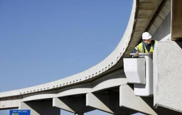 "Yongyut ""Ute"" Ganjanathavat, Senior Structural Engineer, The  Benham Companies, LLC inspects a support column for damage on the Kilpatrick Turnpike bridge near Lake Hefner Parkway after Wednesday's earthquake in Oklahoma City, October 14 , 2010. Photo by Steve Gooch, The Oklahoman"