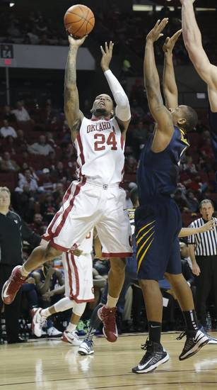 Oklahoma's Romero Osby (24) shoots over West Virginia 's Dominique Rutledge (1) during the first half of the college basketball game between the University of Oklahoma Sooners (OU) and the West Virginia University Mountaineers (WVU) at the Lloyd Noble Center on Wednesday, March 6, 2013, in Norman, Okla. Photo by Chris Landsberger, The Oklahoman