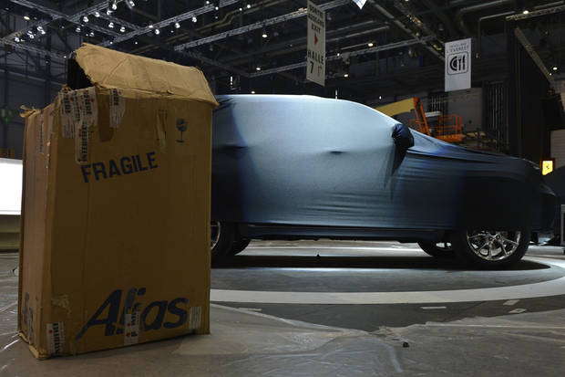 A box stands next to a covered car at the Jeep booth during last preparations prior to the opening of the press preview days at the 83nd Geneva International Motor Show in Geneva, Switzerland, Saturday, March 2, 2013. The Motor Show will open its gates to the public from March 7 to 17, presenting more than 260 exhibitors and more than 130 world and European premieres. (AP Photo/Keystone, Martial Trezzini)