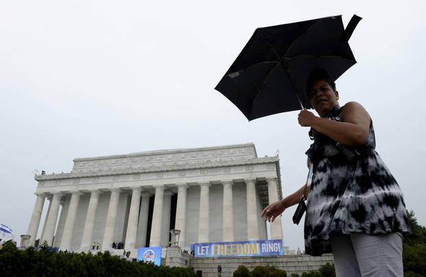A person walks in the rain past the Lincoln Memorial in Washington, Wednesday, Aug. 28, 2013, during the 50th anniversary of the March on Washington. President Barack Obama will speak later Wednesday. (AP Photo/Susan Walsh)