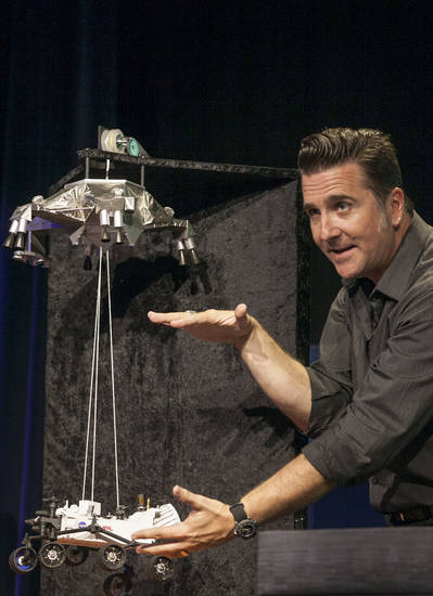 FILE - In this file photo taken Thursday, Aug., 2012, Adam Steltzner, Mars Science Laboratory's entry, descent and landing phase leader at JPL uses a scale model to explains the Curiosity rover's Entry, Descent, and Landing (EDL) during the Mission Engineering Overview news briefing at NASA's Jet Propulsion Laboratory in Pasadena, Calif. Curiosity is scheduled to land on Mars Sunday night, Aug. 5, 2012. (AP Photo/Damian Dovarganes, File)