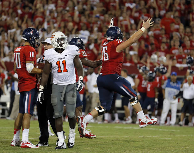 OSU / CELEBRATION: Oklahoma State's Shaun Lewis (11) watches Arizona's Kyle Quinn (76) celebrate at the end of the college football game between the University  of Arizona and Oklahoma State University at Arizona Stadium in Tucson, Ariz.,  Sunday, Sept. 9, 2012. Photo by Sarah Phipps, The Oklahoman