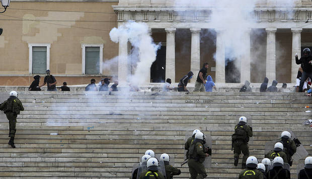 Protesters are chased by riot police during clashes in front of the parliament in Athens, Tuesday Oct. 9, 2012. German Chancellor Angela Merkel got a hostile reception from ordinary Greeks Tuesday when she flew into Athens on her first visit to the country since its debt crisis erupted three years ago. (AP Photo/Nikolas Giakoumidis)