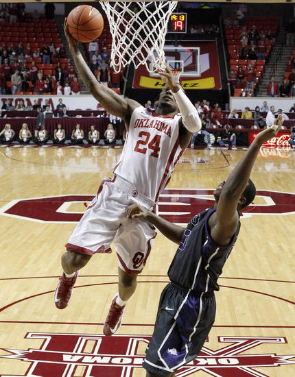 Oklahoma forward Romero Osby (24) goes up for a shot in front of TCU forward Devonta Abron, right, in the first half of an NCAA college basketball game in Norman, Okla., Monday, Feb. 11, 2013. Oklahoma won 75-48.(AP Photo/Sue Ogrocki)