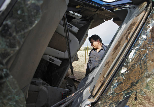 Truck driver Armando Castillo is seen through the busted out windshield of his semi truck as he looks for items to salvage after he was able to survive the tornado the swept him off of I-40 west of El Reno, Tuesday, May 24, 2011. Photo by Chris Landsberger, The Oklahoman