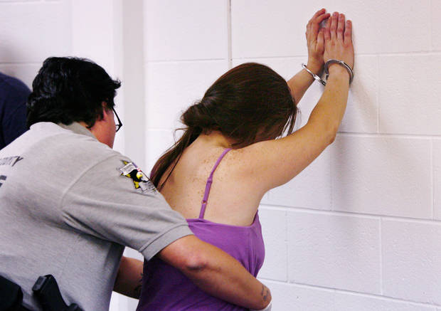 A woman arrested in morning drug raid stands handcuffed against the wall while she is frisked by an Oklahoma County Sheriff's deputy in a processing room Tuesday, June 29, 2010, Photo  by Jim Beckel, The Oklahoman