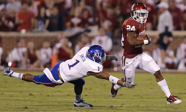 OU's Brennan Clay (24) runs past KU's Lubbock Smith (1) during the college football game between the University of Oklahoma Sooners (OU) and the University of Kansas Jayhawks (KU) at Gaylord Family-Oklahoma Memorial Stadium on Saturday, Oct. 20th, 2012, in Norman, Okla. Photo by Chris Landsberger, The Oklahoman
